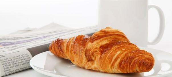 Zeitung, Tasse und Croissant